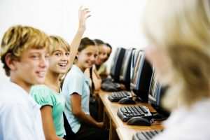 Student raising hand in computer lab